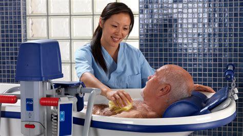 a nurse bathing a male patient. picture 6