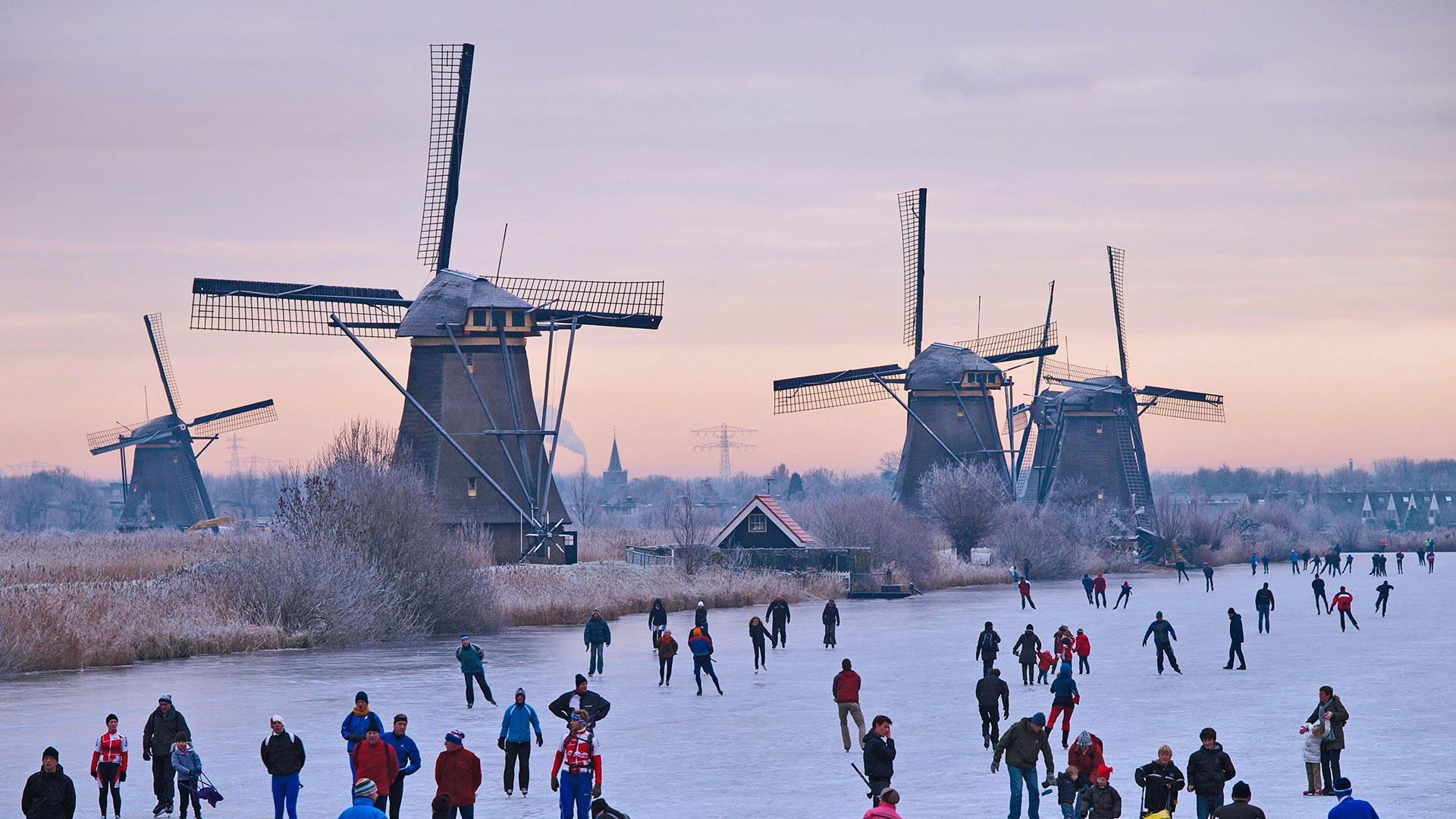 「風車とスケーター」オランダ, キンデルダイク (© Lourens Smak/Alamy)