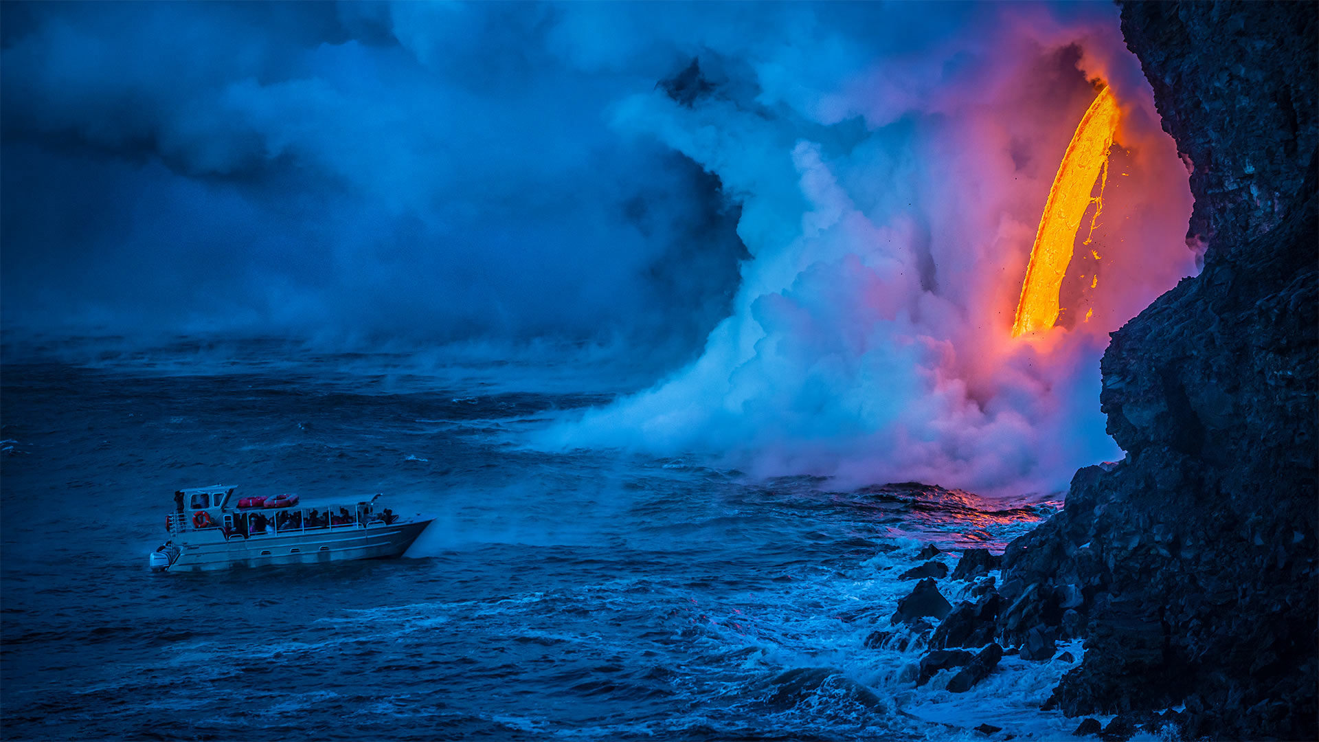 A lava flow hits water as a tour boat passes, Hawaii Volcanoes National Park (© Patrick Kelley/Getty Images)(Bing United States)