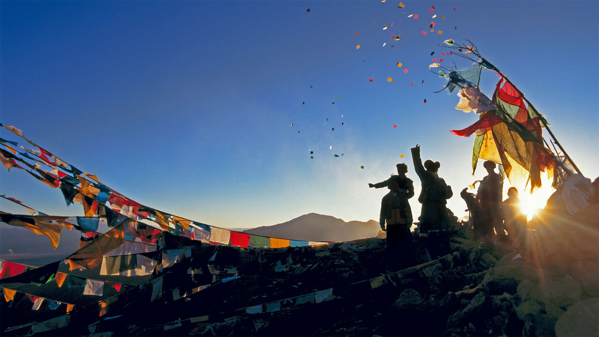 Pilgrims throwing wind horses into the air above Ganden Monastery for the New Year in Tibet, China (© Ian Cumming/plainpicture)(Bing United States)