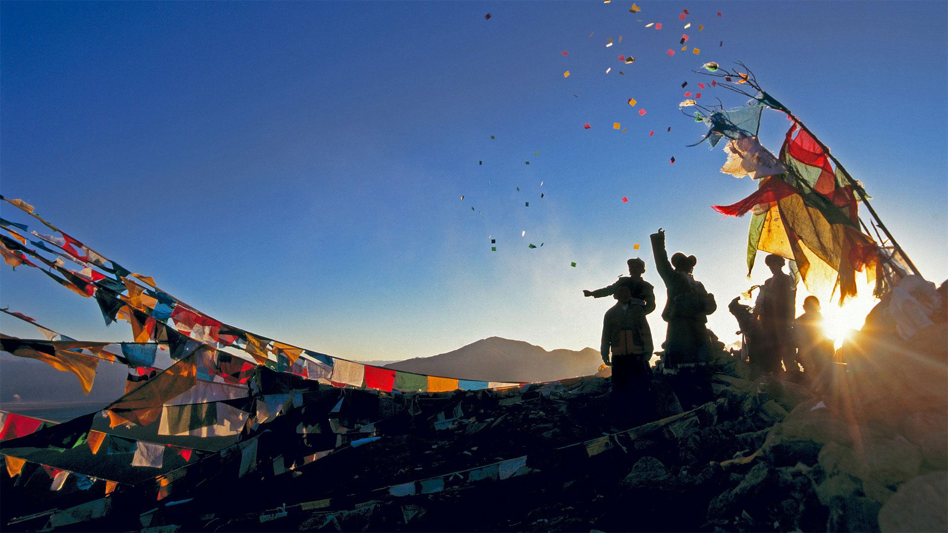 Pèlerins relâchant leurs chevaux du vent dans les airs, au-dessus du monastère de Ganden pour le Nouvel An Tibétain en Chine (© Ian Cumming/plainpicture)(Bing France)