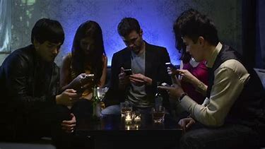 Image result for images of people sitting at table with cell phones